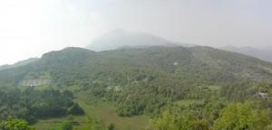"""Panorama pola bitwy widziana z okien klasztoru. Cmentarz, nad nim wzgórze 593, w prawo od niego Głowa Węża, w tle za nimi Monte Cairo - """" jednooki Cyklop"""". Niżej przykryta zielenią """"Dolina Śmierci"""" z farmą D Onofrio."""